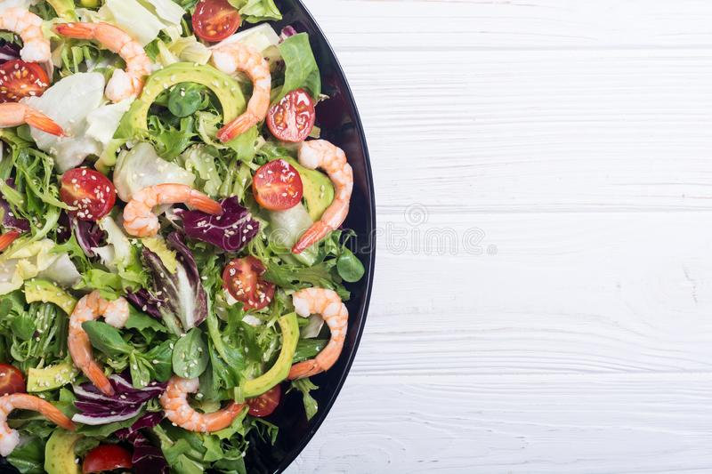 Mix of salad with shrimps avocado and cherry tomatoes . Healthy food background royalty free stock photo