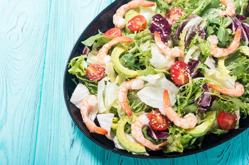 Mix of salad with shrimps avocado and cherry tomatoes . Healthy food background stock photo