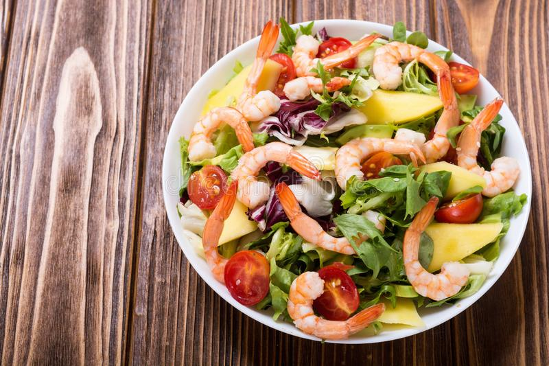 Mix of salad with shrimps avocado and cherry tomatoes . Healthy food background royalty free stock image
