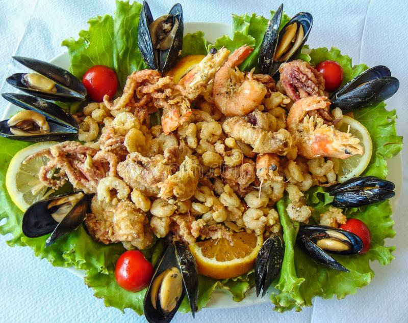 Mix Seafood salad. Served at an restaurant in Saranda coastal city, Albania, fried, sarande, albanian, traditional, lettuce, lemon, tomato, mussel, mussels stock images