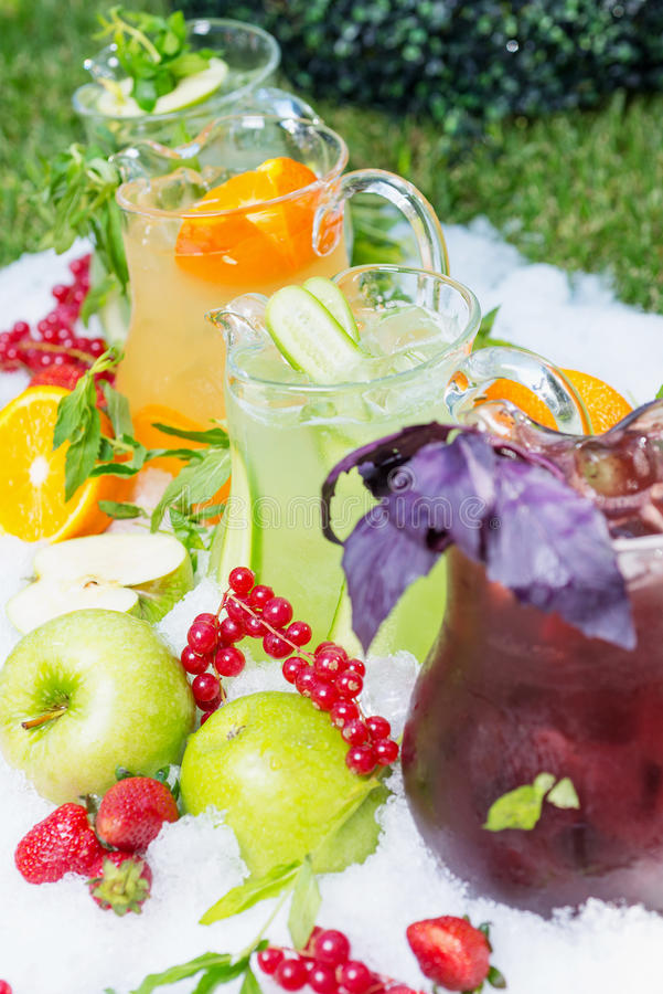 A mix of several bright colored delicious cold. Lemonade carafes of kiwi and orange and strawberry on the table with creative composition of ice berries oranges royalty free stock photos
