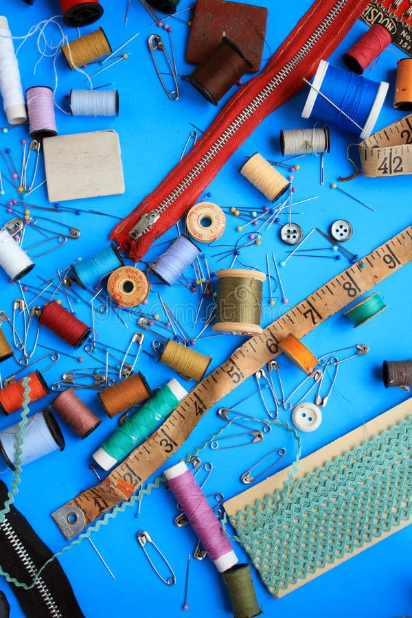 Mix of sewing pins and thread and sewing material. Sewing pins and safety pins different spools of thread. Measuring tape and red zipper. Buttons and other stock images