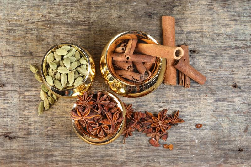 Mix spice in golden metal pot on rustic wood stock photography