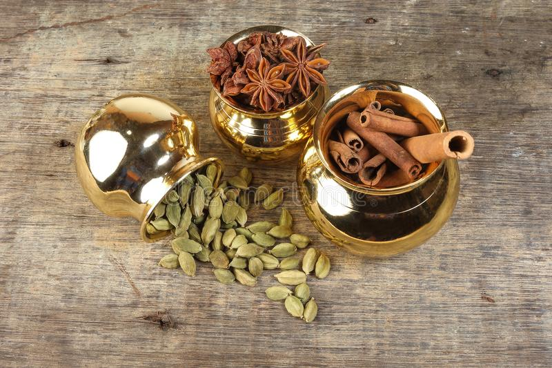 Mix spice in golden metal pot on rustic wood royalty free stock photography