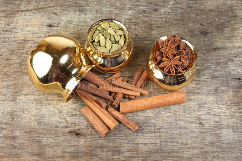 Mix spice in golden metal pot on rustic wood royalty free stock images