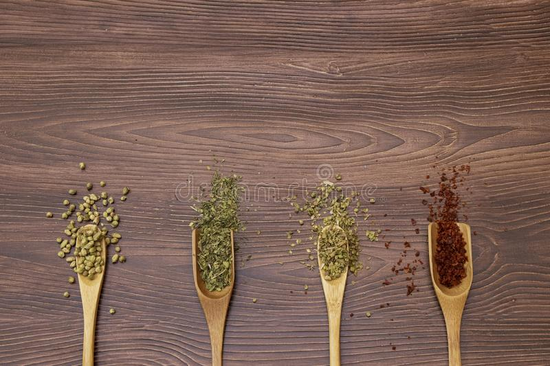 Mix spice, Red pepper, mint and thyme in wooden spoon on wood table background stock photography