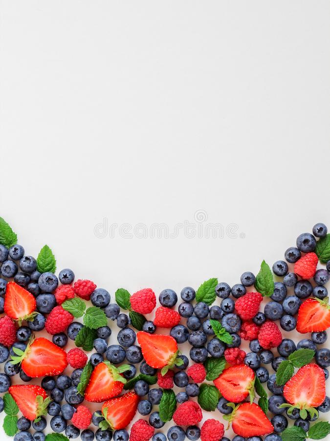 A mix of summer berries arranged neatly on a white background with a large copy spac. A mix of summer berries - strawberries, blueberries and raspberries stock photos