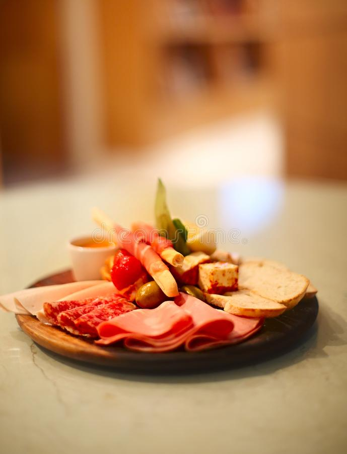 Mix of traditional spanish ham salami, parma ham on grissini bread sticks, marinated vegetables and olives on wooden plate with stock images