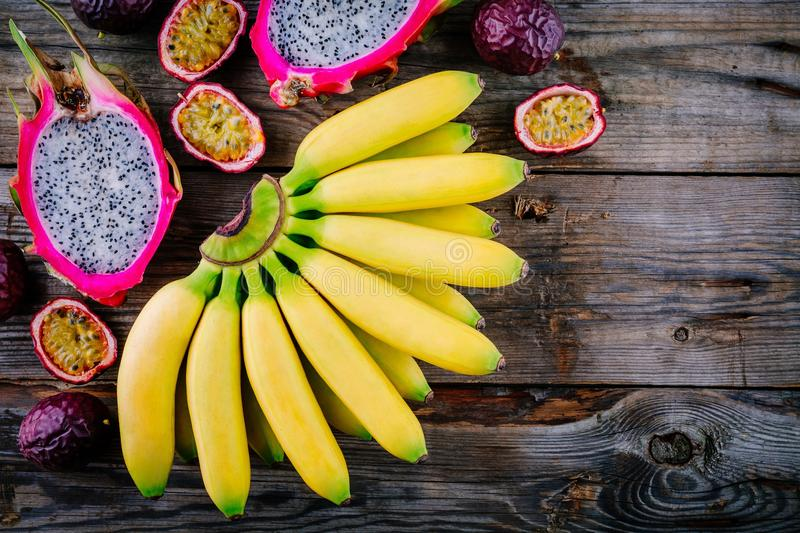 Mix of tropical fruits with banana, passion fruit and dragon fruit on a wooden background. royalty free stock images