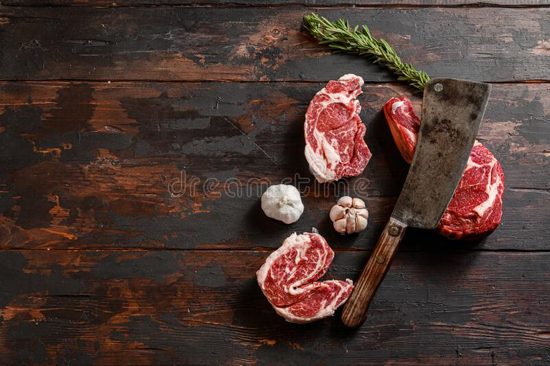 Mix various Cowboy Chuck eye roll Delmonico steak, Entrecote which lies near the cutting knife. Raw beef meat prepared for cooking. Steaks. Beside the royalty free stock photo