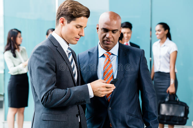 Mixed Asian and Caucasian business team meeting stock photo