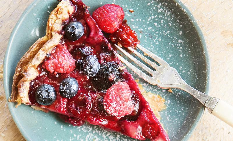 Mixed berries pie on blue ceramic plate royalty free stock photography