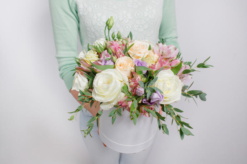 Mixed bouquet of various flowers in a hat box in woman's hands royalty free stock image