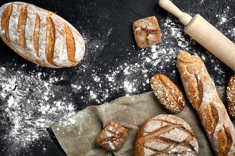 Mixed breads on black table. Top view with copy space. stock images