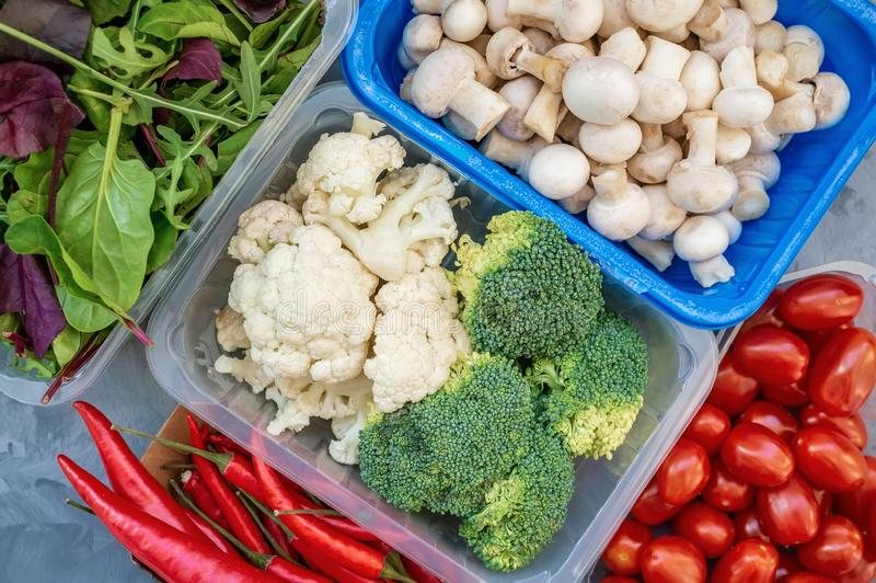Mixed cauliflower and broccoli vegetables, baby salad, mushrooms, peppers, tomatoes and chili in lunch box on wooden royalty free stock images