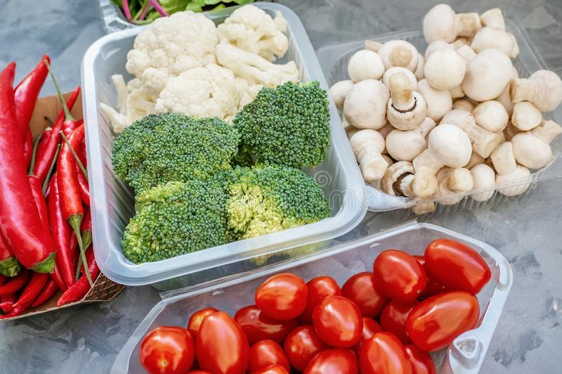 Mixed cauliflower and broccoli vegetables, baby salad, mushrooms, peppers, tomatoes and chili in lunch box on wooden royalty free stock photos