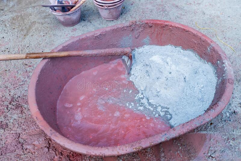 Mixed cement in the bowl. Builders are pouring out of sacks of cement mortar with stone. stock photo