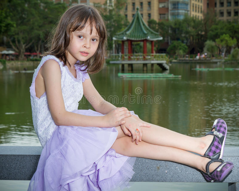 MIxed Chinese girl sitting in front of lake and Chinese pagoda royalty free stock image