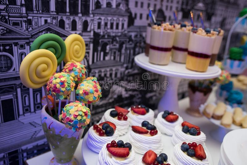 Mixed colored delicious sweets. Colored delicious sweets with cream, biscuits and fruits stock image