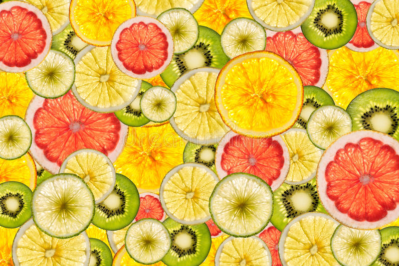 Mixed colorful sliced fruits background back lighted. Mixed colorful sliced fruits as full background back lighted royalty free stock images