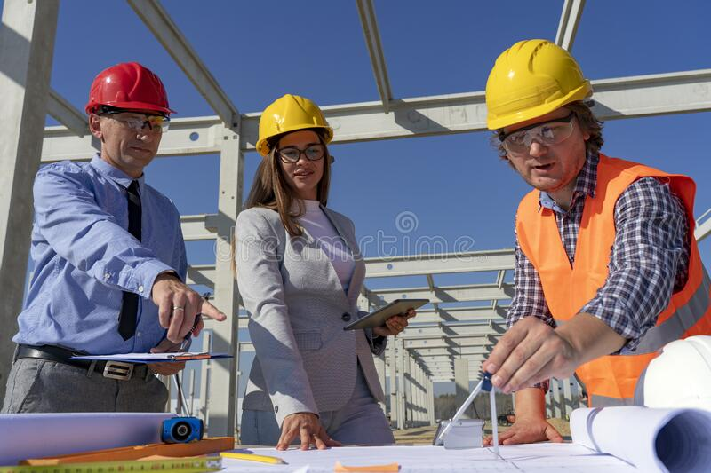 Mixed Construction Business Team in Yellow and Red Hardhats Discuss on Blueprint on Site Under Construction royalty free stock images
