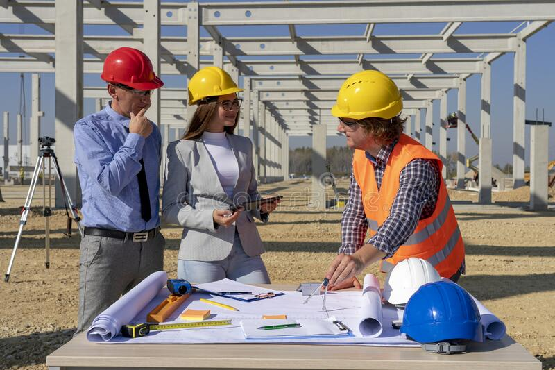 Hardhats Discuss a Project on Site Under Construction stock image