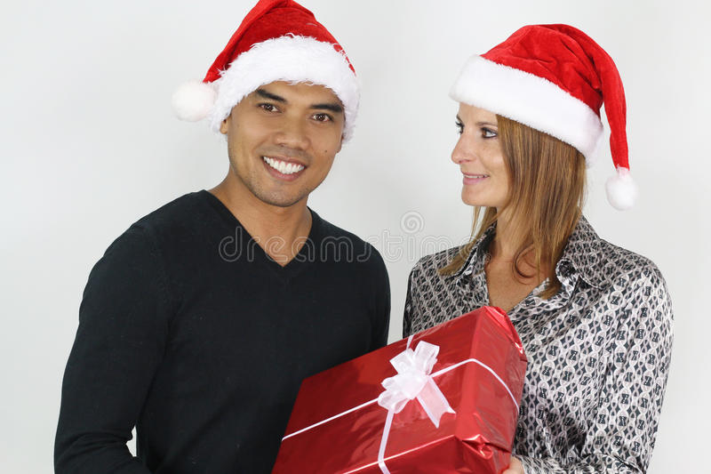 Mixed couple with a Christmas gift. Young mixed couple with a Christmas gift over a white background royalty free stock image