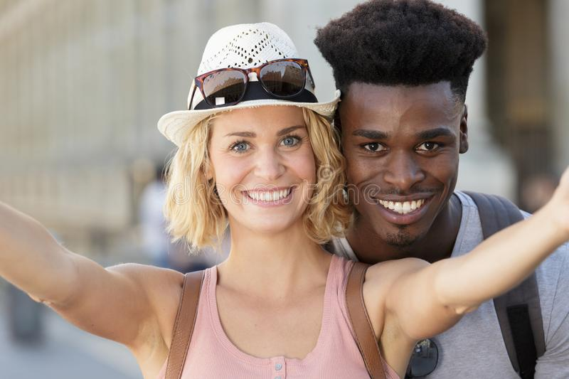 Mixed couple taking selfie with smartphone stock image