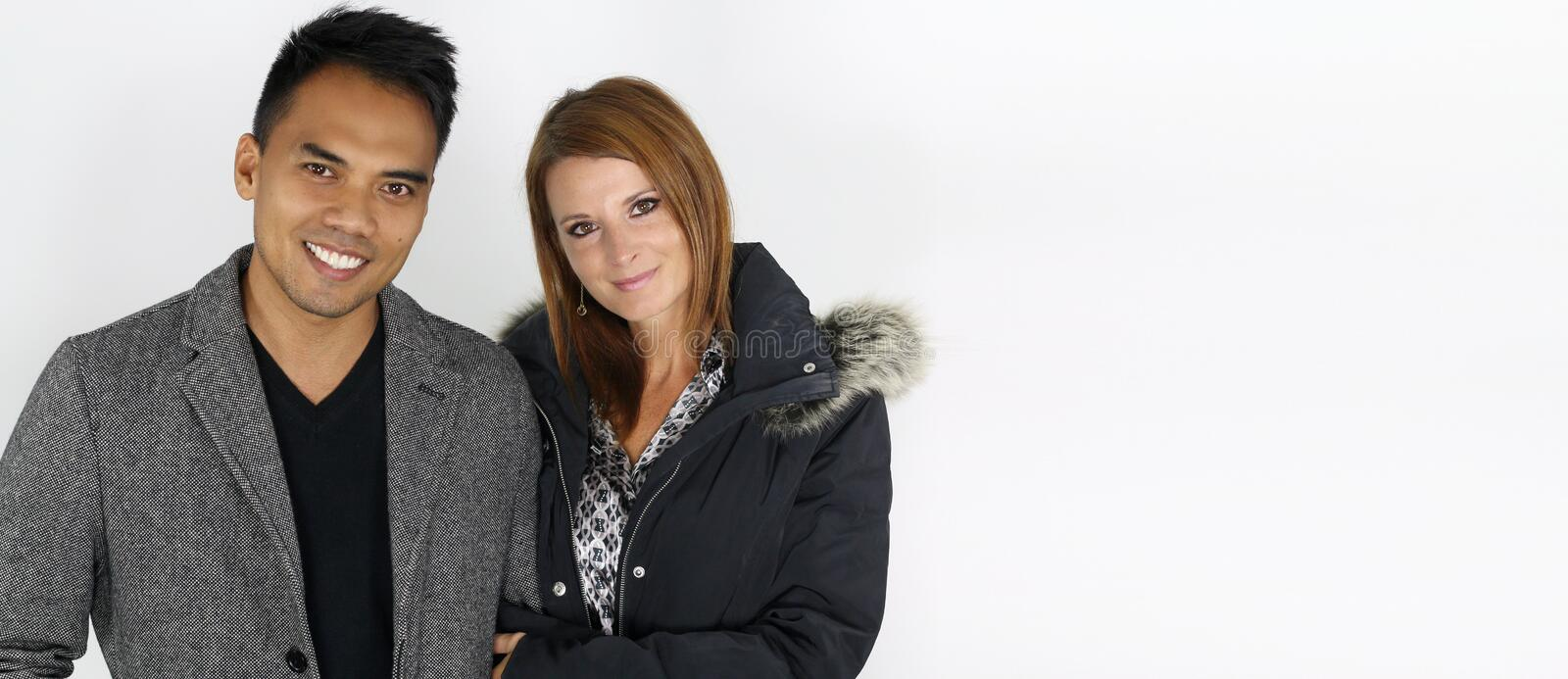 Mixed couple wearing winter jackets. Over a white background stock images