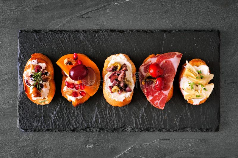 Mixed crostini appetizers with a variety of toppings, top view on a dark slate background. Mixed crostini appetizers with a variety of toppings. Top view on a stock photography