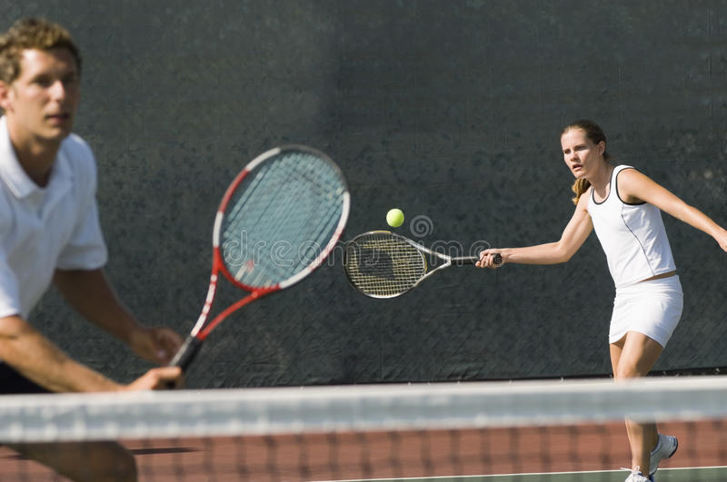 Mixed Doubles Player Hitting Tennis Ball. With partner standing near net stock photos