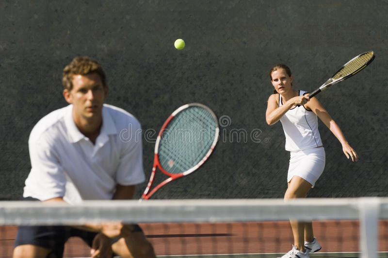 Mixed Doubles Player Hitting Tennis Ball. With partner standing near net royalty free stock photo