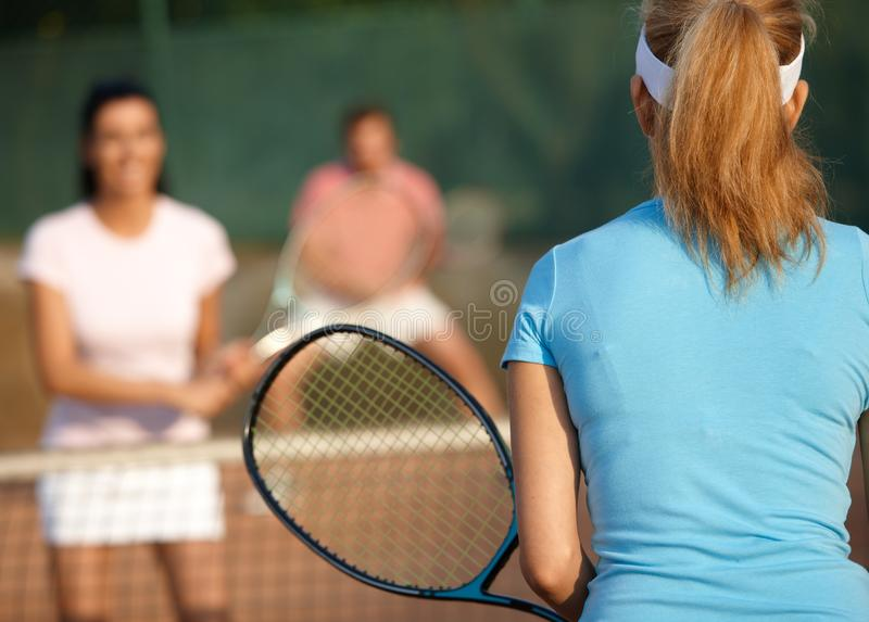 Mixed doubles tennis game. Young companionship playing mixed doubles on tennis court stock photo