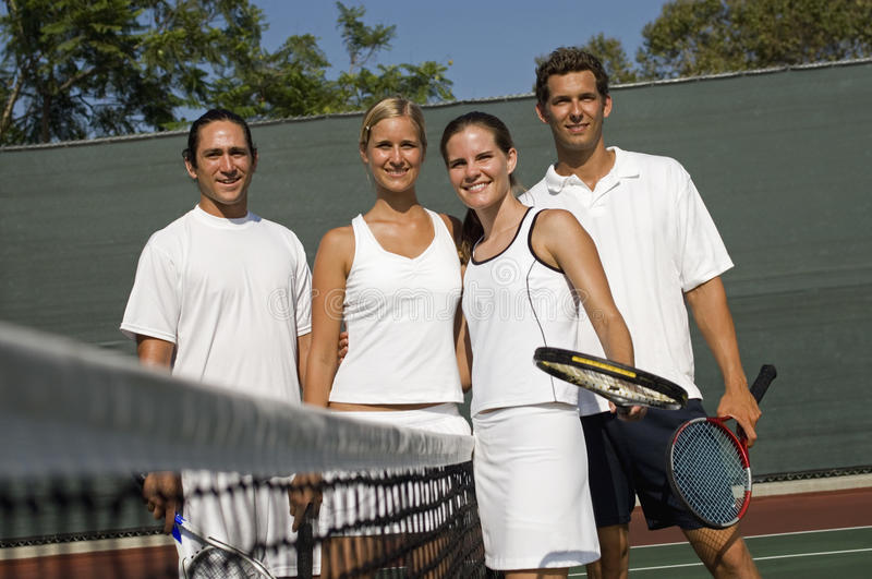 Mixed Doubles Tennis Players. Portrait of mixed doubles tennis players standing by net on tennis court stock photo