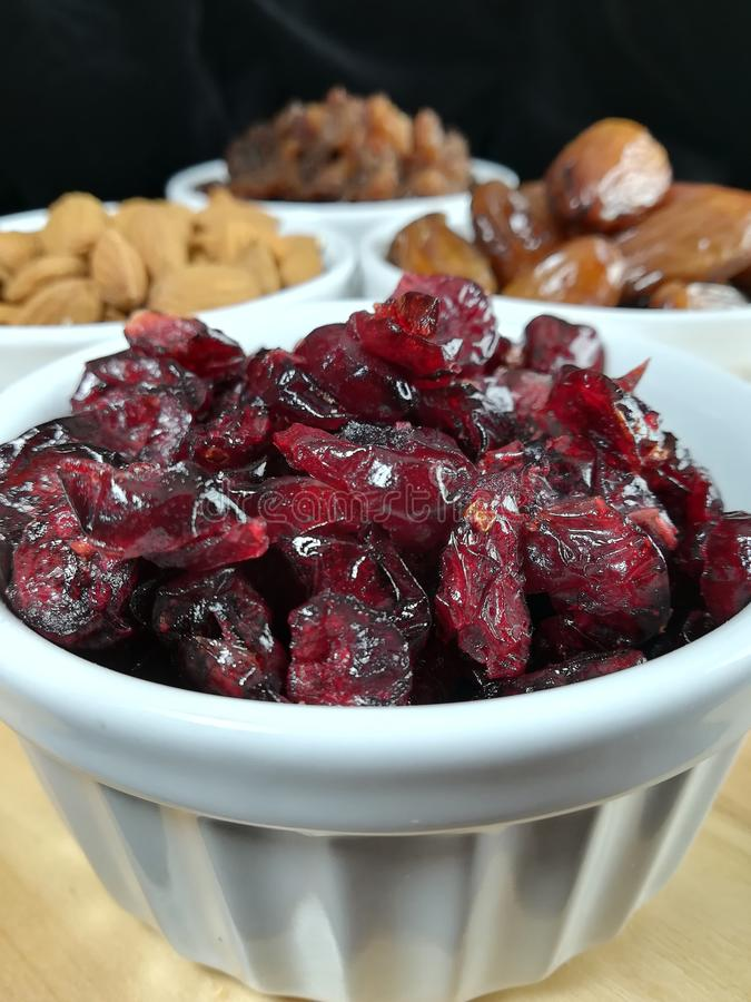 Mixed dried fruits. Assorted dried fruits: cranberries, rasins, almonds, date palm stock photos