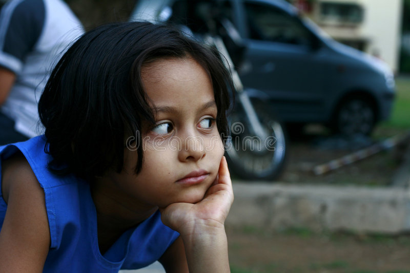 Mixed Emotions. A girl observing something with mixed emotions of anger and discontentment and curiosity royalty free stock photography