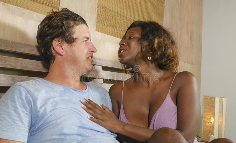 Mixed ethnicity couple in love cuddling together at home in bed with beautiful playful black African American woman and caucasian royalty free stock photography