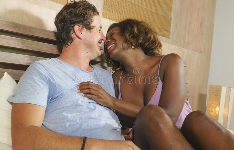 Mixed ethnicity couple in love cuddling together at home in bed with beautiful playful black African American woman and caucasian stock images