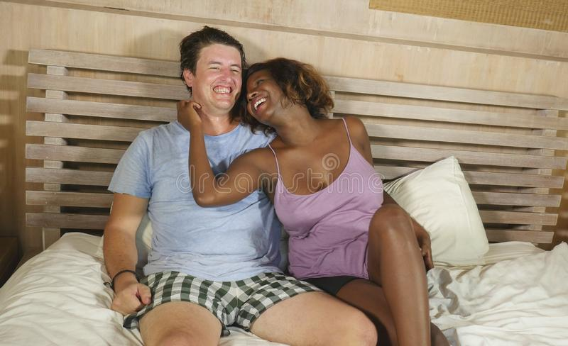 Mixed ethnicity couple in love cuddling together at home in bed with beautiful playful black afro American girlfriend or wife and stock photos