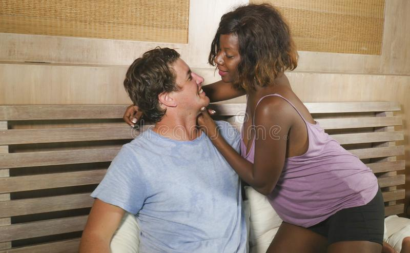 Mixed ethnicity couple in love cuddling together at home in bed with beautiful playful black afro American woman and white stock photo