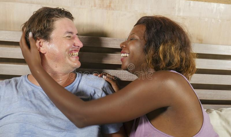 Mixed ethnicity couple in love cuddling together at home in bed with beautiful playful black afro American woman and white stock photography