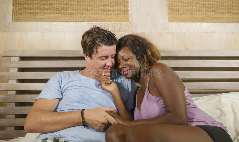 Mixed ethnicity couple in love cuddling together at home in bed with beautiful playful black afro American woman and white royalty free stock photo