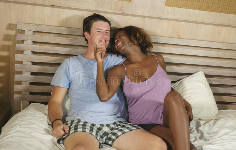 Mixed ethnicity couple in love cuddling together at home in bed with beautiful playful black afro American woman and white royalty free stock photos
