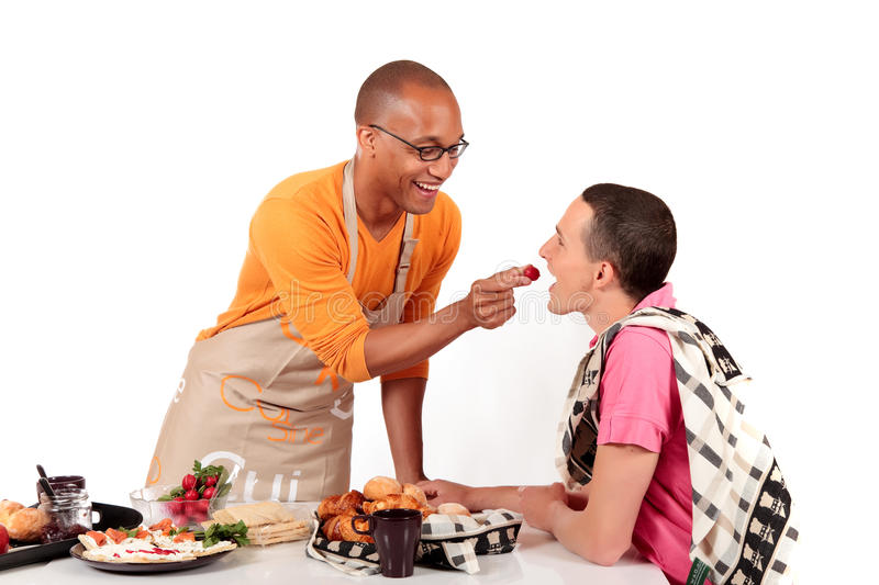Mixed ethnicity gay couple kitchen. Attractive young mixed ethnicity gay, homosexual couple, Caucasian and African American in kitchen, preparing breakfast royalty free stock image