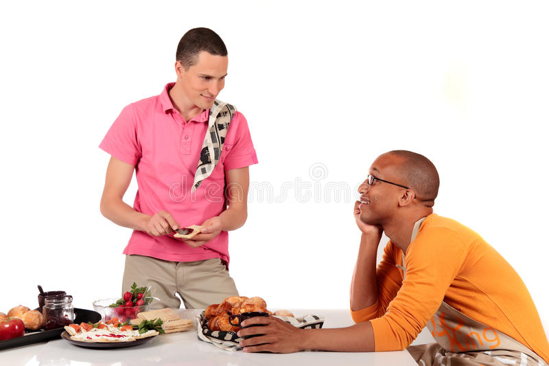 Mixed ethnicity gay couple kitchen. Attractive young mixed ethnicity gay, homosexual couple, Caucasian and African American in kitchen, preparing breakfast royalty free stock photos