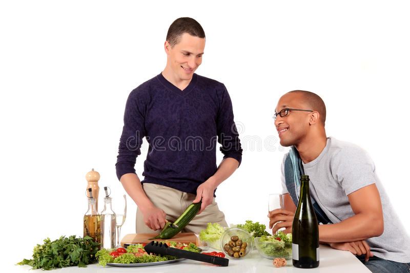 Mixed ethnicity gay couple kitchen. Attractive young mixed ethnicity gay, homosexual couple, Caucasian and African American in kitchen, preparing salad for royalty free stock images