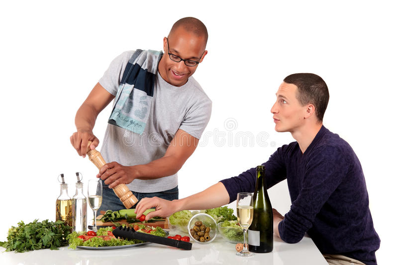 Mixed ethnicity gay couple kitchen. Attractive young mixed ethnicity gay, homosexual couple, Caucasian and African American in kitchen, preparing salad for stock photography