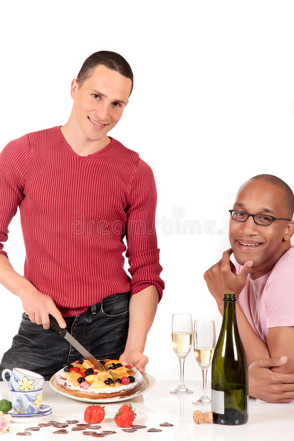 Mixed ethnicity gay couple kitchen. Attractive young mixed ethnicity gay, homosexual couple, Caucasian and African American in kitchen, enjoying a fruit pie and royalty free stock images