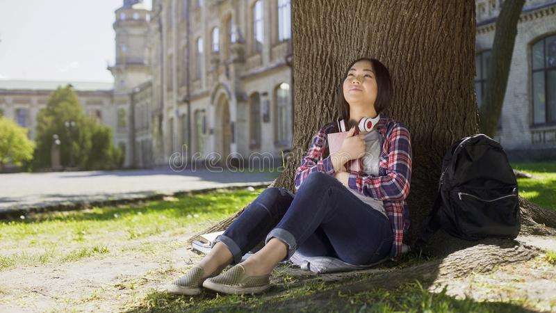 Mixed female reading book under tree, pressing it against chest, favorite book royalty free stock photos