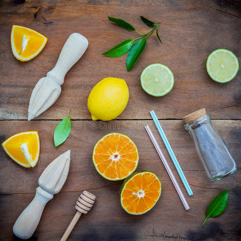 Mixed fresh citrus fruits and orange leaves background. Ingredients for summer citrus juice with juicer and glass bottle .Fresh l royalty free stock images